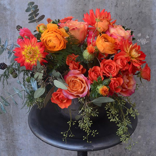 Orange, red, and coral flowers with blackberries in a dark gray vase
