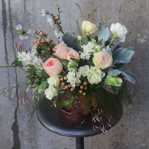 Pastel pink and white flowers with greenery and thistles in a specialty copper vase