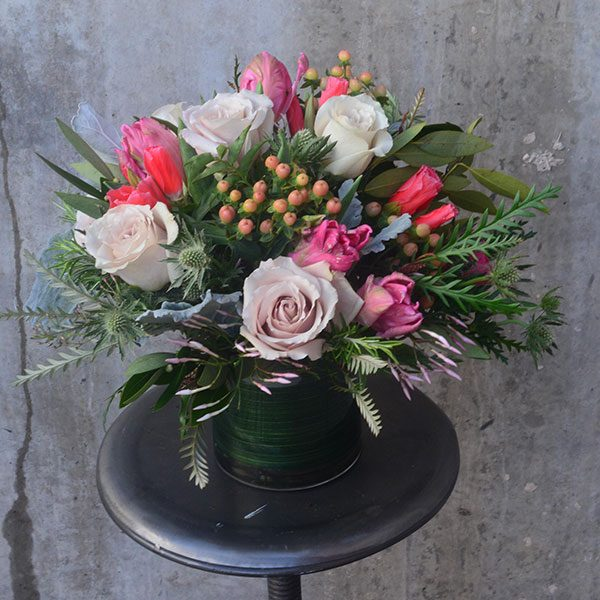 A range of pink flowers, greenery, and thistles in a leaf-wrapped clear vase