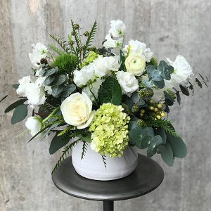 White roses, eucalyptus, thistles, and more in a white ceramic vase