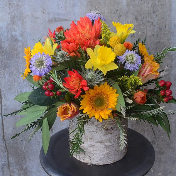 Periwinkle, yellow, and coral flowers all gathered in a birch vase from your local florist