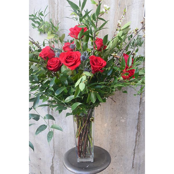 Red roses and abundant greenery in a tall clear vase