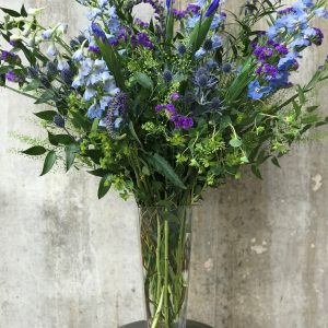Purple and periwinkle flowers with greenery and blackberries in a tall clear vase
