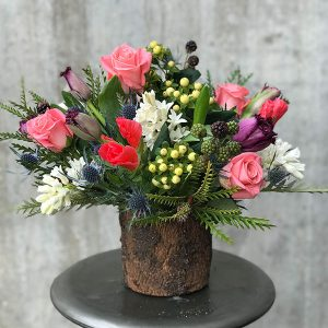 Pink, red, and white flowers with thistles and blackberries in a birch vase