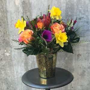 Vibrant yellow and purple flowers in a hammered gold vase